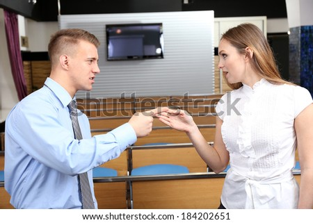 Work colleagues arguing at conference hall - stock photo