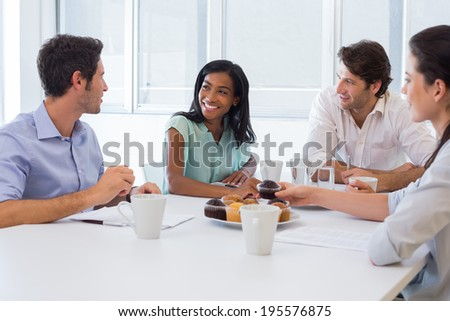 Work colleagues chatting in board room while enjoying coffee and muffins in the office - stock photo