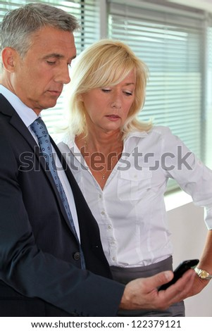 Work colleagues looking mobile - stock photo
