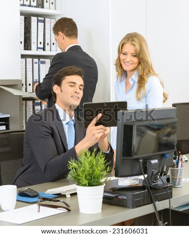 Work colleagues sitting at the office desk looking at a tablet - stock photo