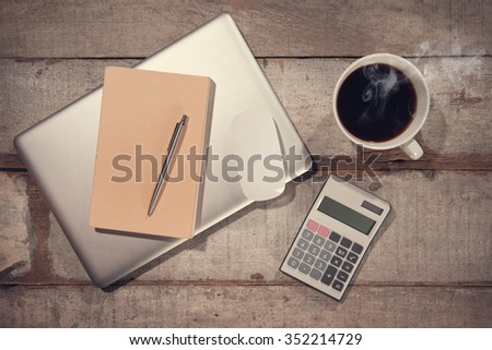 Work desk with laptop computer, diary book, pen calculator and hot coffee cup. Top view rustic wooden table background in vintage toned. - stock photo