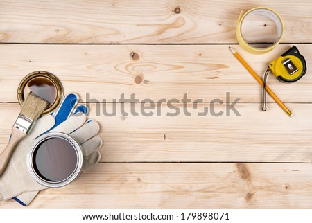 Work gloves, a brush, a can of paint, propelling pencil and ruler on a wooden background