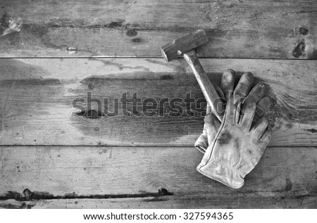Work gloves holding hammer on wooden work table- vintage black and white processing - stock photo