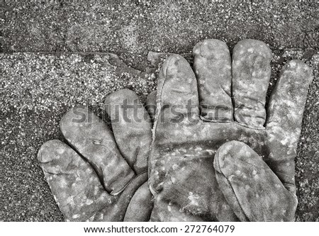 Work gloves lying on shingles. Black and white image. - stock photo