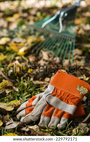 work gloves with a rake in the background - stock photo