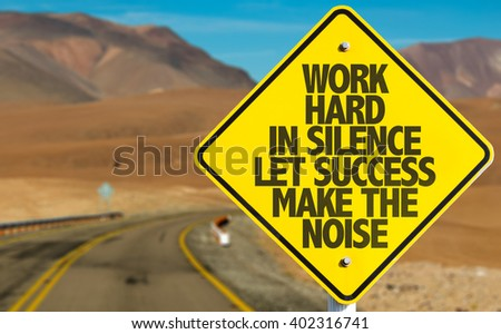 Work Hard in Silence Let Success Make the Noise sign on desert road - stock photo