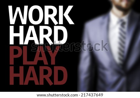Work Hard Play Hard written on a board with a business man on background - stock photo