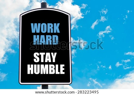 WORK HARD STAY HUMBLE  motivational quote written on road sign isolated over clear blue sky background with available copy space. Concept  image