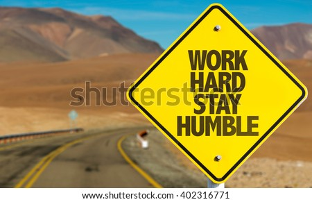 Work Hard Stay Humble sign on desert road - stock photo