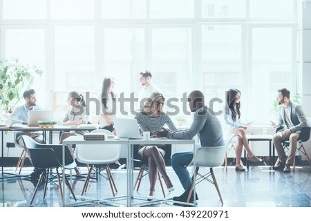 Work in action. Group of young business people working and communicating with each other while sitting at their working places in office  - stock photo