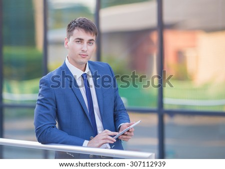 Work in full swing. Successful businessman standing in the street holding a laptop