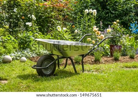 Work in garden-wheelbarrow on the front of flower bed - stock photo