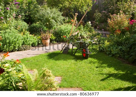 Work in summer garden in the morning with wheelbarrow, shovel and rake - horizontal - stock photo
