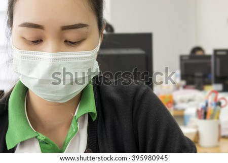 work in the office, Asian Young woman wearing the face mask for protection [blur and selective focus background] - stock photo
