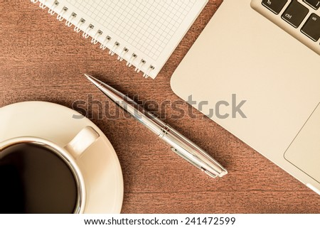 Work in the office, coffee cup with laptop and a pen with a notebook on the wooden table. In yellow tone - stock photo