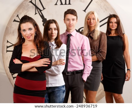 Work in the women's collectives. Four women and one man were gathered together. Students. Group of people of different nationalities on the background of the clock. Against the background of the group - stock photo