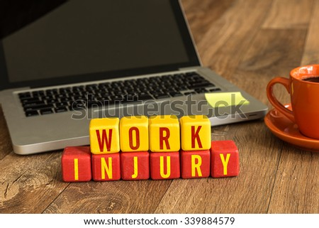 Work Injury written on a wooden cube in a office desk - stock photo