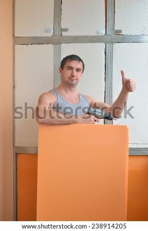 Work insulates the wall and shows thumb - stock photo