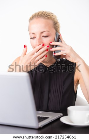 Work late into the night. Business woman yawning while talking on the mobile home and checking some information on her laptop computer in office. White cup of coffee on the desk.  - stock photo