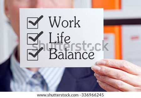 Work Life Balance - Businesswoman holding card with text in the office - stock photo