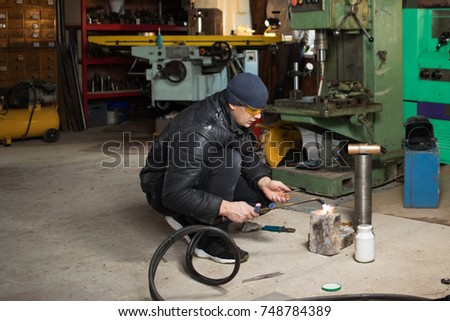 Work man  metal product at home garage, with flame burning gas welding