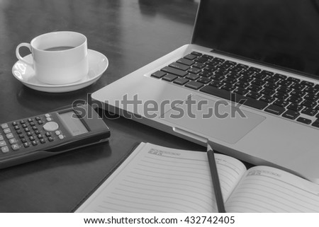 work on a wooden desk with a laptop and nootbook and calculator monochrome