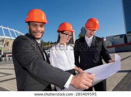 Work on the construction site. Three confident business architect in protective helmet standing in a row at the construction site while the African architect with a smile looking at the camera