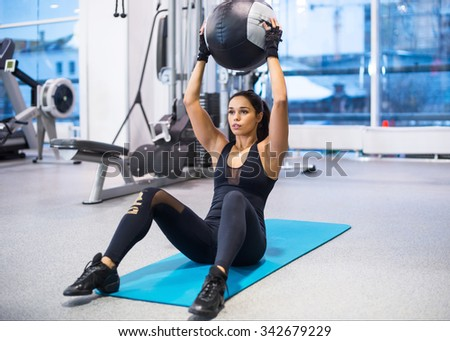 Work out fitness woman doing sit ups abs abdominal crunches exercises with ball - stock photo