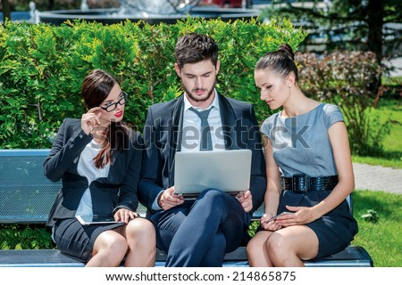 Work outside the office. Three successful businessmen in formal  dress sitting on the street to discuss business and keep computers in their hands. Young businessmen talking to each other