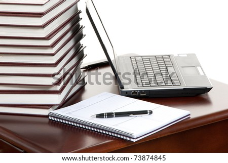 Work place table with stacks of real books on it and modern lap top, pen and textbook lying near on a white background. - stock photo