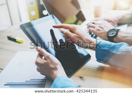 Work Process in Modern Office. Young Account Manager Working at Wood Table with New Business Project.Touching Screen Digital Tablet.Man using Laptop.Horizontal. Film effect. Blurred background - stock photo