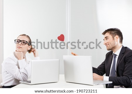 Work romance between two business people holding a heart - stock photo