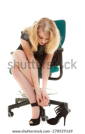 Work stoppage and foot feet pain ache. Businesswoman sitting on chair and taking shoes off. Business concept. Isolated on white. Studio shot. - stock photo