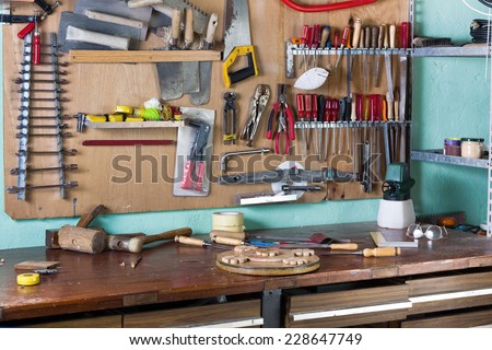 work table of a carpenter with many tools hanging in the background / workbench of handyman - stock photo