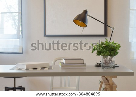 work table with book lamp, and vase at home - stock photo