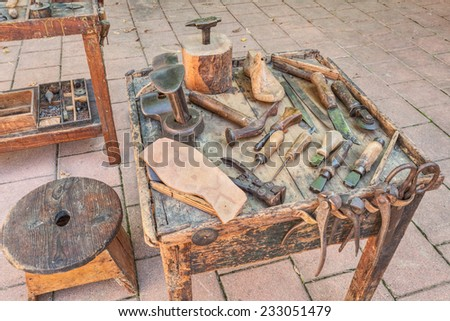 work table with old tools of the artisan shoemaker to cut and shape the leather to make shoes  - stock photo
