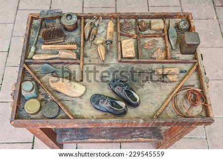 work table with small shoes for children and old tools of the artisan shoemaker for repair and finishing shoe   - stock photo