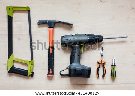 Work Tools for home renovation - long nose pliers, saw, hammer, electric screwdriver, screwdriver on beige background. Repair concept - stock photo