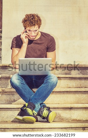 Work. Wearing dark brown T shirt, blue jeans, black sneakers, a young sexy guy with curly hair is sitting on stairs outside office, crossing legs, talking on mobile phone, working on laptop computer.  - stock photo