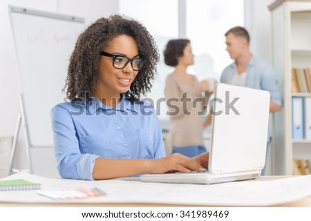 Work with laptop. Young attractive woman is sitting at the desk and working on her laptop while her colleagues are having a coffee break. - stock photo