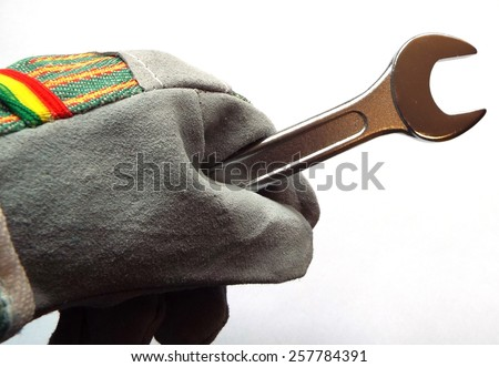 Work - Wrench in a hand with working glove, diagonal - stock photo