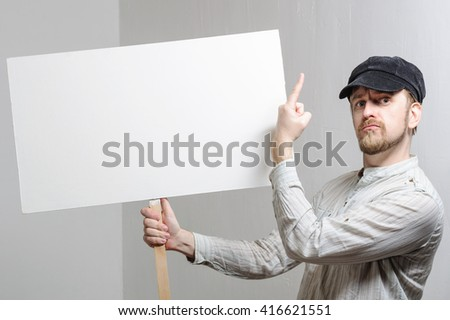 Work young man points finger on a blank banner - isolated on white. - stock photo