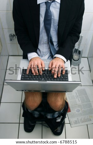 workaholic business man working on his lap top while using the toilet - stock photo