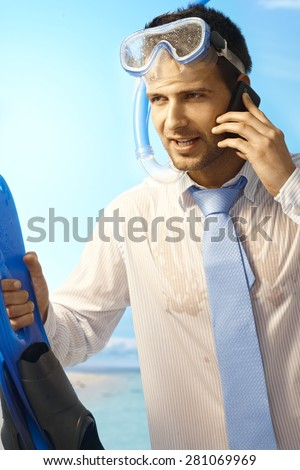 Workaholic young businessman on mobilephone on summer holiday, wearing shirt and tie and scuba diving equipments. - stock photo