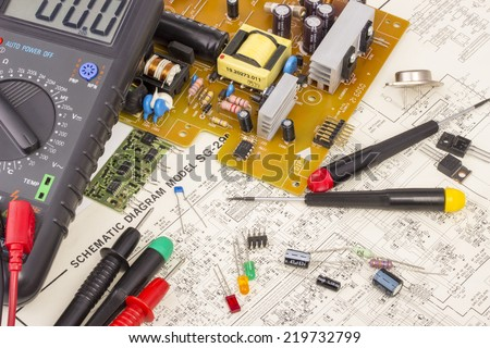Workbench for electronics repair, multimeter, electronic components, electronic board, screwdrivers, transistors, integrated circuits, capacitors, all on electronic diagram background - stock photo