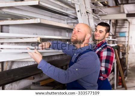 Workem in blue uniform are choosing PVC window profiles from a rack - stock photo