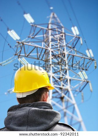 worker against power lines - stock photo