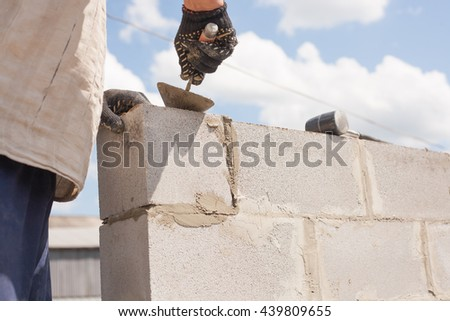 worker aligns with a spatula, lay brick cinder blocks.