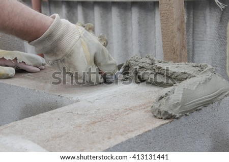 worker aligns with a spatula, lay brick cinderblock. - stock photo