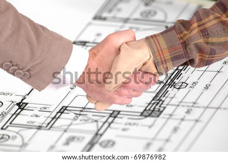 Worker and a businessman shaking hands over house renovation plans house renovation contract deal and plans - stock photo